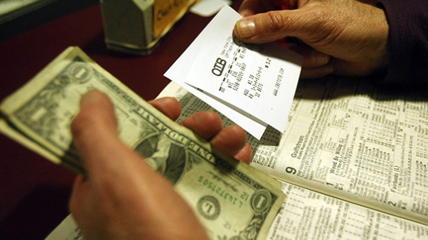 NEW YORK - MARCH 1:  A man holds his betting slips and money at an Off-Track Betting (OTB) parlor in Midtown Manhattan March 1, 2008 in New York City. The board that oversees New York City's OTB operations voted last week to close all 71 parlors by mid-June since the city does not want to subsidize the gambling outposts. State officials are contesting the ruling.  (Photo by Mario Tama/Getty Images)